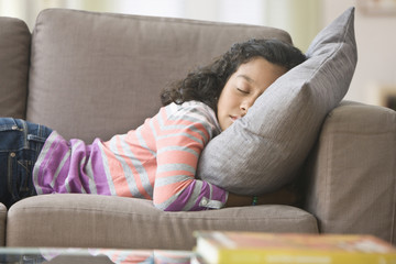 Hispanic girl napping on sofa