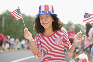 Hispanic girl waving American flags on Fourth of July