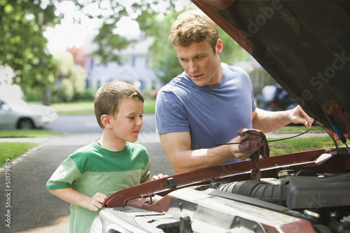 Caucasian boy watching father work on car engine