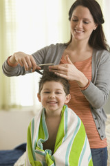 Caucasian woman cutting son's hair