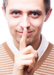 A man holds his index finger near the mouth