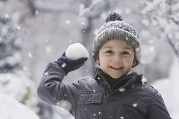 Caucasian boy throwing snowball