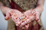 Caucasian woman with Indian henna tattoos on her hands holding wedding rings