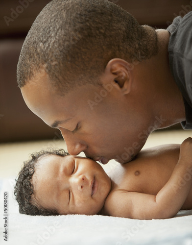 Father kissing newborn baby