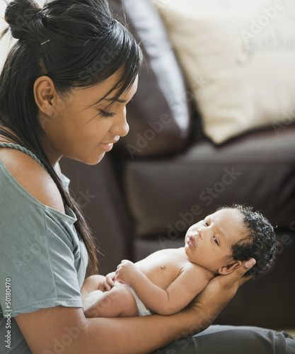 Mixed race mother holding newborn baby