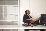 Black businessman playing guitar at desk