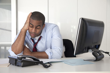 Tired Black businessman sitting at desk