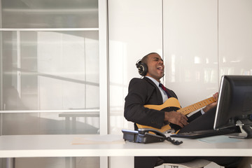 Black businessman playing guitar at desk