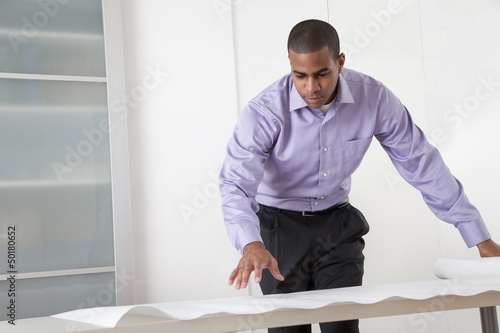 Black architect looking at blueprints