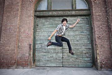 Mixed race man jumping on urban sidewalk
