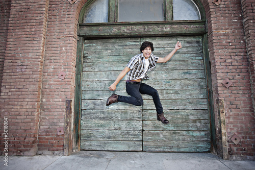 Mixed race man jumping on urban sidewalk