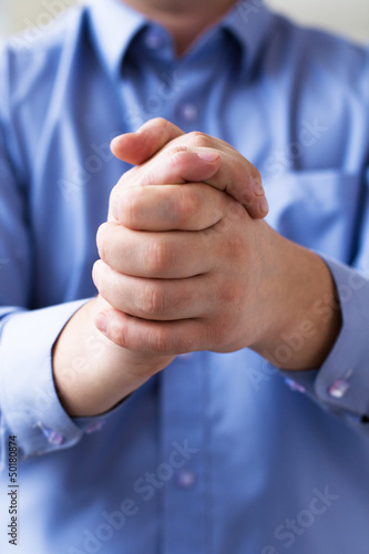 A man holds his hands folded