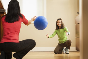 Mother and daughter playing with ball