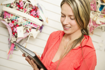 Hispanic woman using digital tablet in clothing store