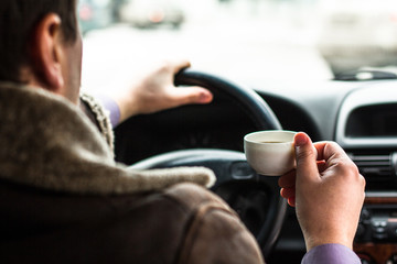 A man sitting in a car and holding a cup of coffee