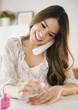 Hispanic woman talking on phone and painting fingernails