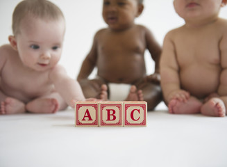 Babies sitting with alphabet blocks