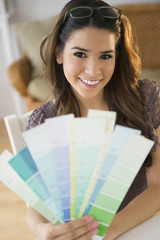 Hispanic woman holding paint swatches