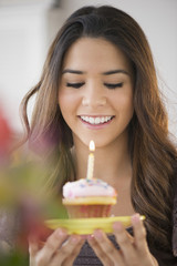 Hispanic woman blowing out cupcake candle