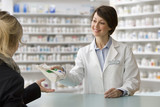 Caucasian pharmacist handing prescription to customer