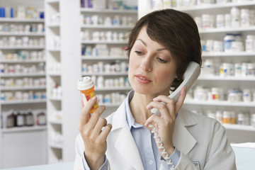 Caucasian pharmacist holding pill bottle and talking on telephone