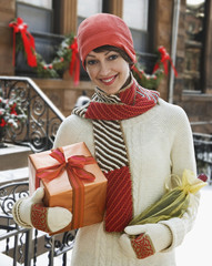 Caucasian woman standing in snow holding Christmas gifts