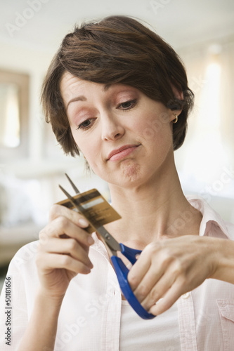Caucasian woman cutting up credit cards
