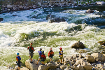 Caucasian family standing near rapids in river