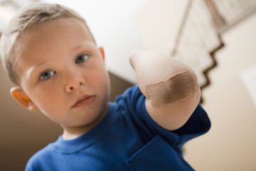 Caucasian boy with bandage on elbow