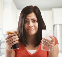 Caucasian woman holding glasses of soda and water
