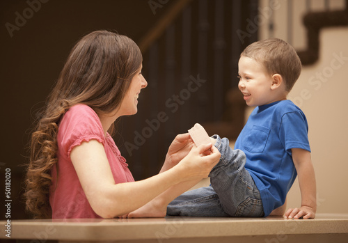 Caucasian mother putting bandage on son's knee