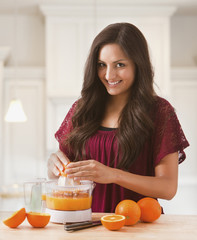 Mixed race woman making fresh orange juice