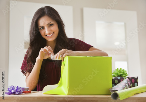 Mixed race woman wrapping gift