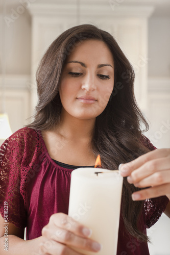 Mixed race woman lighting candle
