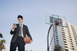 Mixed race businessman holding basketball and text messaging on cell phone