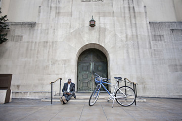 Businessman sitting on steps near bicycle