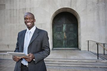 Businessman using digital tablet on urban sidewalk