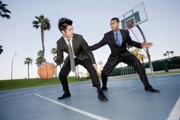 Businessmen playing basketball outdoors