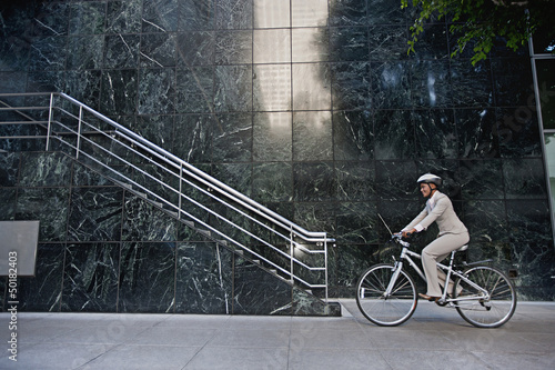 Businesswoman riding bicycle on sidewalk