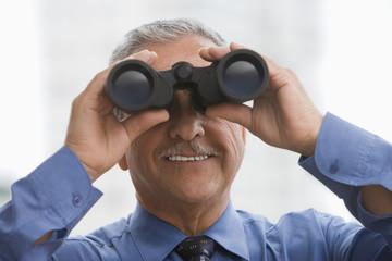 Hispanic businessman using binoculars