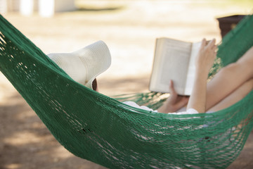 Young woman reading a book while relaxing in a hammock