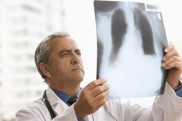 Hispanic doctor looking at x-ray