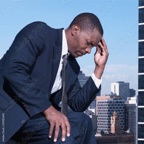 Black businessman thinking outdoors