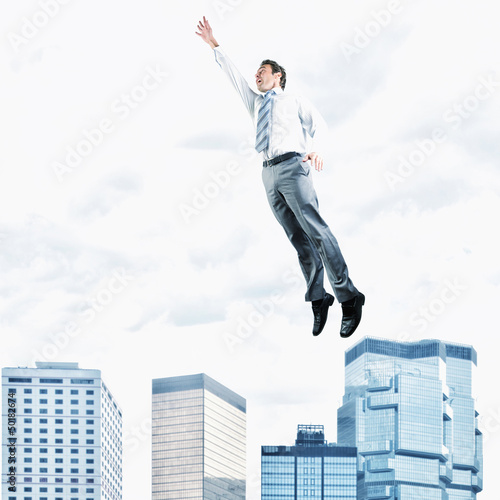 Hispanic businessman jumping in air