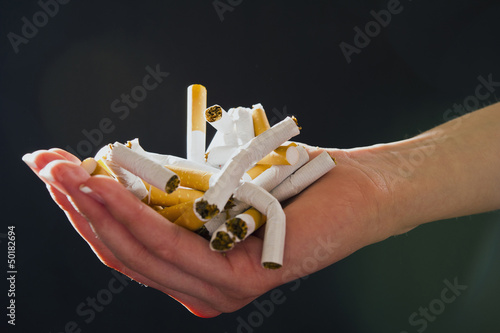 Pacific Islander woman holding crushed cigarettes