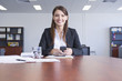 Hispanic businesswoman in conference room with cell phone