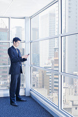 Asian businessman text messaging on cell phone