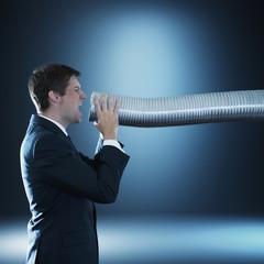 Caucasian businessman shouting into tube