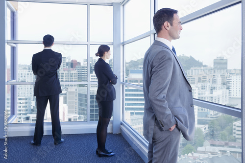 Business people looking out office windows