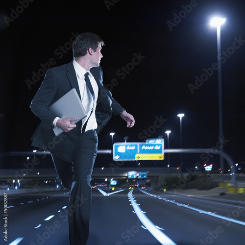 Caucasian businessman running on urban freeway at night